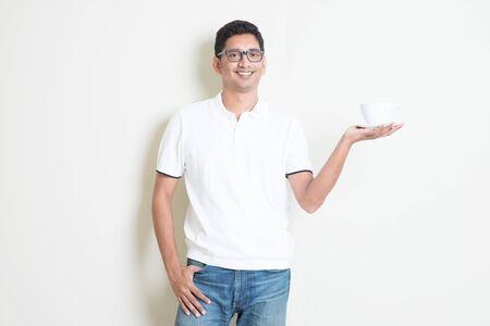 Indien tenant une tasse de café à portée de main. Homme asiatique debout sur un fond ordinaire avec des ombres et un espace de copie. Beau modèle masculin.