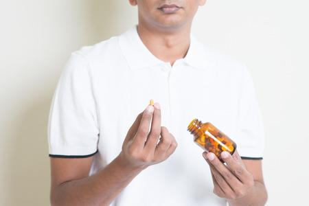medicina: Chico indio enfermo que toma cápsula de medicina. Hombre asiático que se coloca en el fondo plano con la sombra y espacio de la copia.