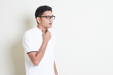 Portrait of Indian guy sore throat, hand on neck clearing throat. Asian man standing on plain background with shadow and copy space. Handsome male model. Stock Photo