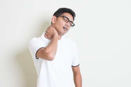 head pain: Portrait of tired Indian guy massaging his neck with painful face expression. Asian man standing on plain background with shadow and copy space. Handsome male model.