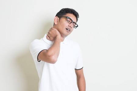 collo: Ritratto di ragazzo indiano stanco massaggiando il collo con espressione del viso doloroso. Asian uomo in piedi su sfondo chiaro con ombra e lo spazio della copia. Modello maschio bello.