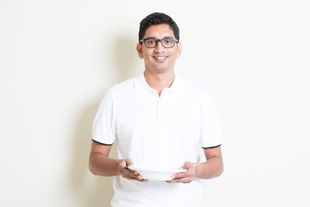 holds: Dining concept. Indian chef holding an empty plate on hand, ready for food. Asian man standing on plain background with shadow and copy space. Handsome male model.