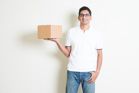 Indian man smiling and holding delivery courier box, standing on plain background with shadow. Asian handsome guy model.
