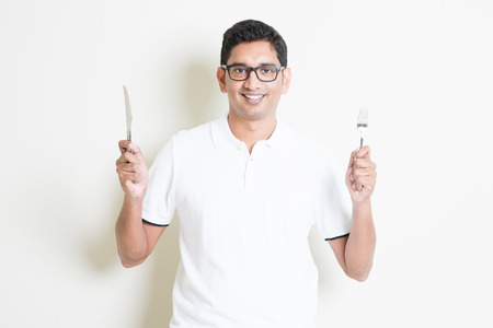 Dining concept. Indian guy holding cutlery fork and knife on hand, hungry for food. Asian man standing on plain background with shadow and copy space. Handsome male model. Stock Photo