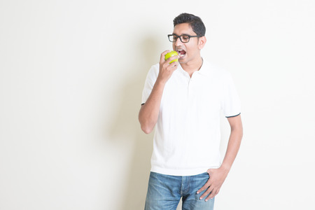 niño parado: Man healthcare concept. Indian guy eating a green apple. Asian standing on plain background with shadow and copy space. Handsome male model.
