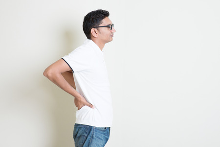 chronic pain: Portrait of Indian guy back pain, holding spine with hands. Asian man standing on plain background with shadow and copy space. Handsome male model. Stock Photo