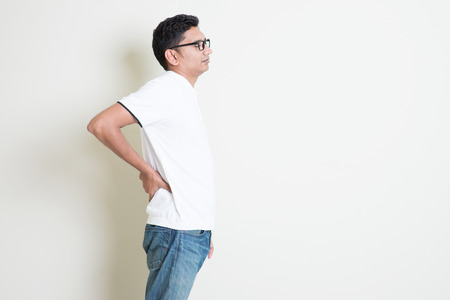 chronic back pain: Portrait of Indian guy backache, holding spine with hand. Asian man standing on plain background with shadow and copy space. Handsome male model. Stock Photo