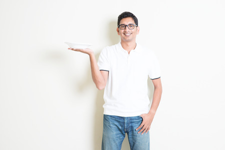healthy men: Dining concept. Indian waiter holding an empty plate on hand, ready for food. Asian man standing on plain background with shadow and copy space. Handsome male model.