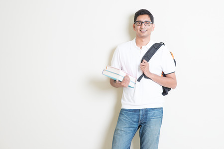 indians: Portrait of adult Indian university student with books and bag. Asian man standing on plain background with shadow and copy space. Handsome mixed race male model.