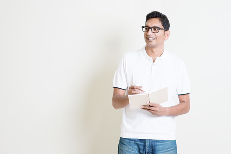 Portrait of Indian guy taking note on book, looking at side and smiling. Asian man standing on plain background with shadow and copy space. Handsome male model.