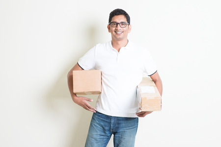 asian guy: Courier delivery service concept. Happy Indian man received brown boxes, standing on plain background with shadow. Asian handsome guy model. Stock Photo