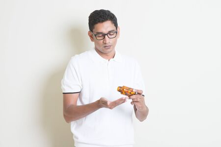 taking medicine: Sick Indian guy taking tablet medicine. Asian man standing on plain background with shadow and copy space.