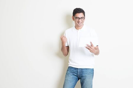 asian guy: Portrait of excited Indian guy using tablet pc and celebrate his success . Asian man standing on plain background with shadow and copy space. Handsome male model.
