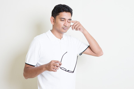 tired eyes: Portrait of Indian guy take off eyeglasses and rubbing his tired eyes. Asian man standing on plain background with shadow and copy space. Handsome male model. Stock Photo