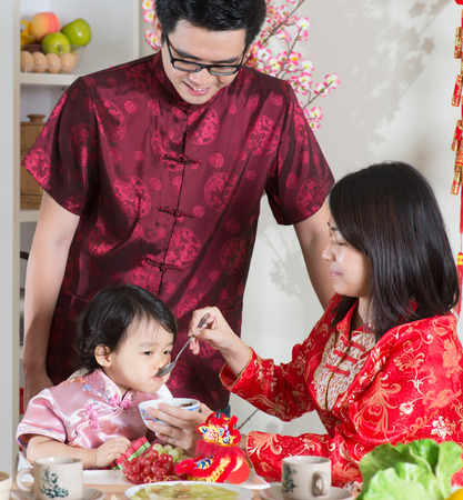 reunion dinner: Chinese New Year, reunion dinner. Happy Asian Chinese family with red cheongsam dining at home.