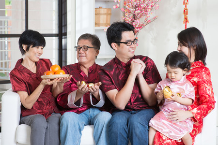 Celebrating Chinese new year. Happy Asian multi generations family in red cheongsam reunion and greeting at home. Stock Photo