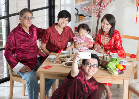 chinese woman: Chinese New Year celebration, reunion dinner. Happy Asian Chinese multi generation family with red cheongsam selfie while dining at home.