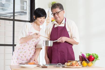 Aziatische volwassen paar het bereiden van voedsel in de keuken. Senioren wonen levensstijl thuis.