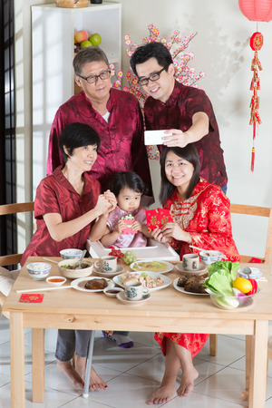 reunion dinner: Happy Chinese New Year, taking selfie at reunion dinner. Happy Asian Chinese multi generation family with red cheongsam dining at home.