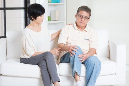 lesionado: Dolor de rodilla hombre edad asiática, sentado en el sofá con la mujer en el hogar. Familia china, jubilado mayor dentro del estilo de vida de estar.