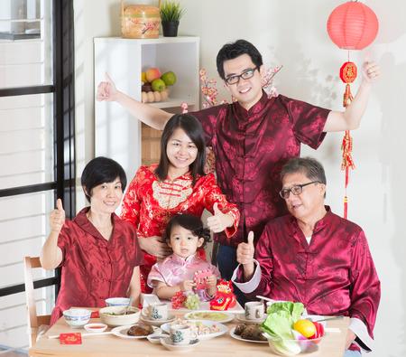 Chinees Nieuwjaar, reünie diner. Gelukkige Aziatische Chinese multi-generatie familie met rode cheongsam dineren thuis.