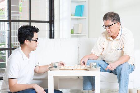 jugando ajedrez: Familia china jugando al ajedrez chino (Xiang Qi) en casa, padre mayor y el hijo adulto. Foto de archivo