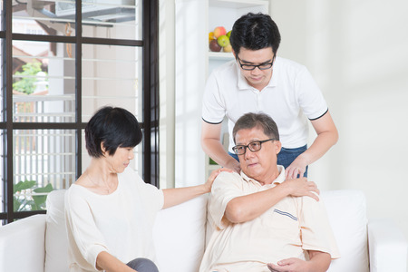 senior man on a neck pain: Asian old man shoulder pain, sitting on sofa with wife, son massaging father shoulder. Chinese family, senior retiree indoors living lifestyle at home.