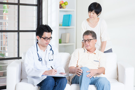 retiree: Doctor and patient. Asian old man consult family doctor, sitting on sofa. Senior retiree indoors living lifestyle.