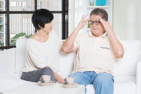 Aziatische oude man hoofdpijn, zittend op de bank met een vrouw thuis. Stockfoto