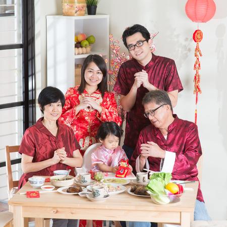 Spring seizoenen Chinees Nieuwjaar, reünie diner. Gelukkige Aziatische Chinese multi-generatie familie met rode cheongsam groet tijdens een diner thuis. Stockfoto