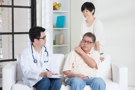 senior man on a neck pain: Doctor and patient. Asian old people consult family doctor, sitting on sofa. Senior retiree indoors living lifestyle.