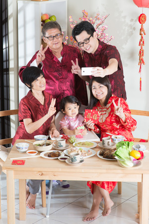 reunion dinner: Celebrating Chinese New Year, taking selfie at reunion dinner. Happy Asian Chinese multi generation family with red cheongsam dining at home. Stock Photo