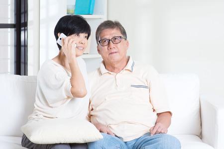 Aziatische hogere paar bellen op telefoon, met behulp van smartphone. Familie wonen levensstijl thuis.