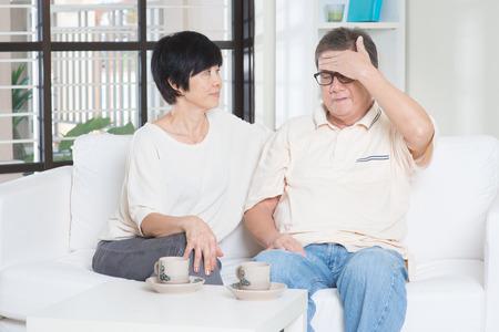 headache: Portrait of mature Asian man having headache, sitting on sofa with wife at home, senior retiree indoors living lifestyle.