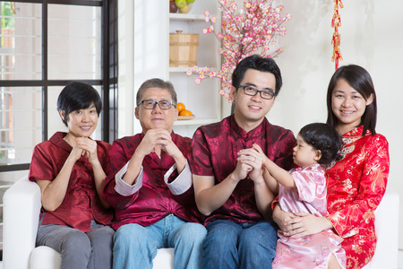 blessing: Celebrating Chinese new year. Happy Asian multi generations family in red cheongsam reunion and greeting at home. Stock Photo