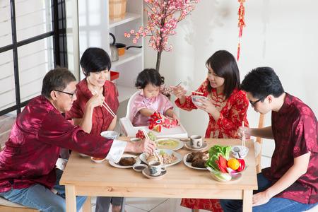 comidas: Celebraci�n de A�o Nuevo chino, cena de reuni�n. Familia multi generaci�n asi�tica con comedor cheongsam rojo en el pa�s.