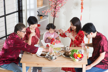 family indoors: Celebrating Chinese New Year, reunion dinner. Asian multi generation family with red cheongsam dining at home.