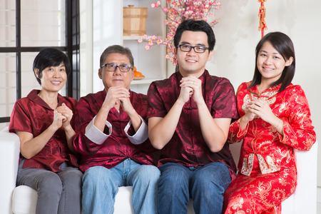 celebrate year: Happy Chinese new year. Happy Asian family in red cheongsam reunion and greeting at home.