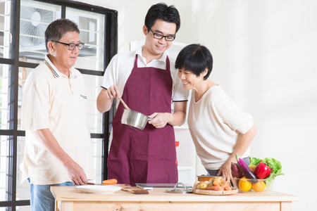 asian cook: Asian adult son preparing meal for his senior parents at kitchen. Family living lifestyle at home. Stock Photo