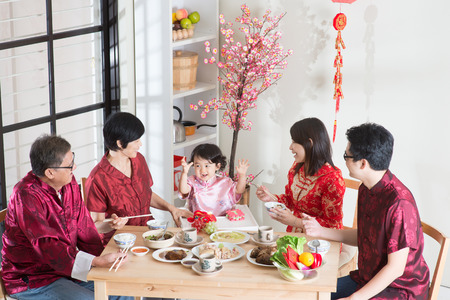 Célébration du Nouvel An chinois, dîner de retrouvailles. Famille asiatique heureux multi génération chinoise de rouge salle cheongsam à la maison.