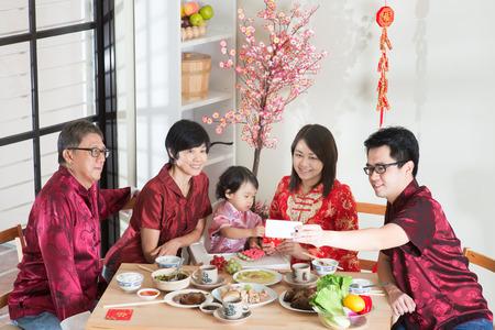 ni�as chinas: Celebraci�n de A�o Nuevo chino, cena de reuni�n. Familia multi generaci�n china asi�tica feliz con selfie cheongsam rojo mientras cena en casa.