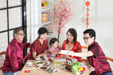multi generation family: Celebrating Chinese New Year, reunion dinner. Happy Asian Chinese multi generation family with red cheongsam selfie while dining at home. Stock Photo