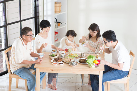 家人: 亞洲快樂中國幾代人多的家庭用餐在家裡。 版權商用圖片