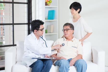 Aziatische zieke oude man raadplegen huisarts, zittend op de bank. Stockfoto