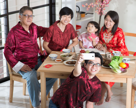 reunion dinner: Chinese New Year, reunion dinner. Happy Asian Chinese multi generation family with red cheongsam selfie while dining at home. Stock Photo