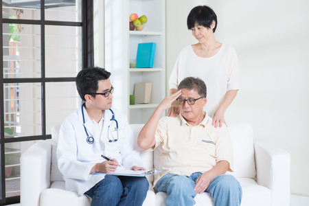 retiree: Doctor and patient. Asian old man headache, consult family doctor, sitting on sofa. Senior retiree indoors living lifestyle. Stock Photo