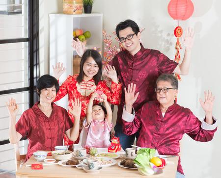 familia cenando: Año Nuevo chino, cena de reunión. Familia asiática feliz múltiples generación china con comedor cheongsam rojo en el país.