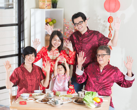 multi generation family: Chinese New Year, reunion dinner. Happy Asian Chinese multi generation family with red cheongsam dining at home.