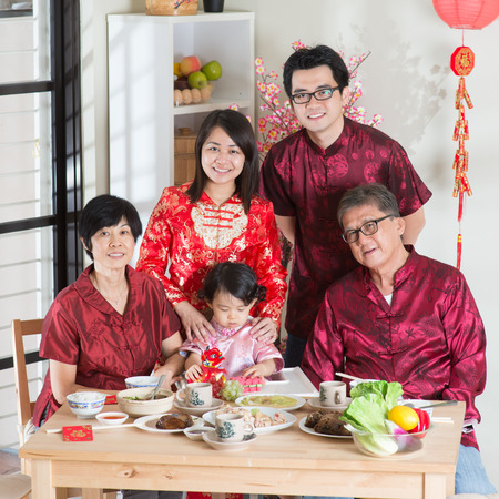 reunion dinner: Spring seasons Chinese New Year, reunion dinner. Happy Asian Chinese multi generation family with red cheongsam taking group photo while dining at home.