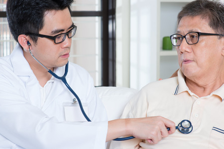 Sick Asian elder man consult family doctor, sitting on sofa.